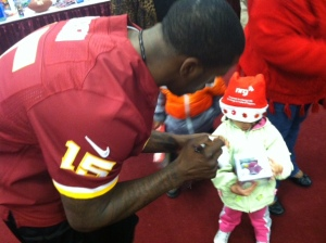 Wide receiver Josh Morgan, a DC native, signs a miniature football for a child. (Credit: Kimberly Suiters/All-News 99.1 WNEW)