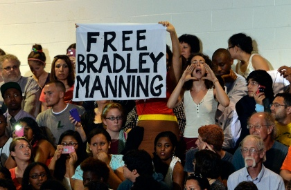 A woman shouts at US President Barack Obama as others display a banner asking for the freedom of Wikileaker Bradley Manning.  (credit: JEWEL SAMAD/AFP/Getty Images)