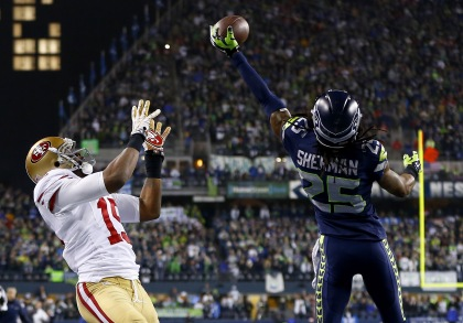 Richard Sherman of the Seahawks tips the ball up in the air as outside linebacker Malcolm Smith catches it to clinch the victory against the 49ers. (Credit: Jonathan Ferrey/Getty Images)
