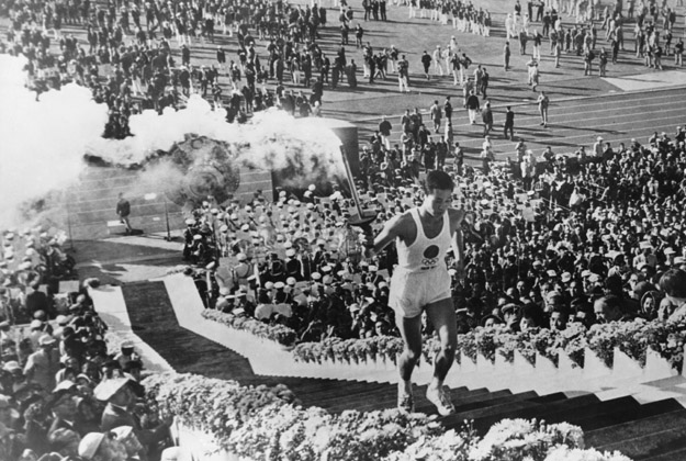 Olympic flame torchbearer Yoshinori Sakai mounts the steps to light the cauldron at the opening ceremony of the Summer Olympic Games at the National Olympic Stadium, Tokyo, 10th October 1964.