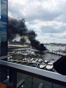 Photo taken by a witness of a boat on fire in the Baltimore Inner Harbor. (Photo credit: @CiERROR)