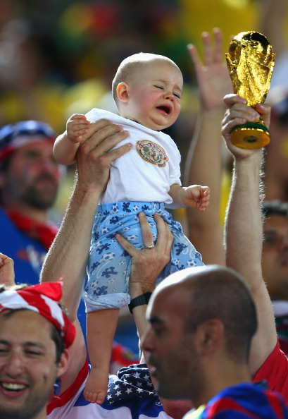 A young fan is held up next to a replica of the World Cup trophy during the 2014 FIFA World Cup Brazil Group G match between Ghana and the United States (credit: Michael Steele/Getty Images)