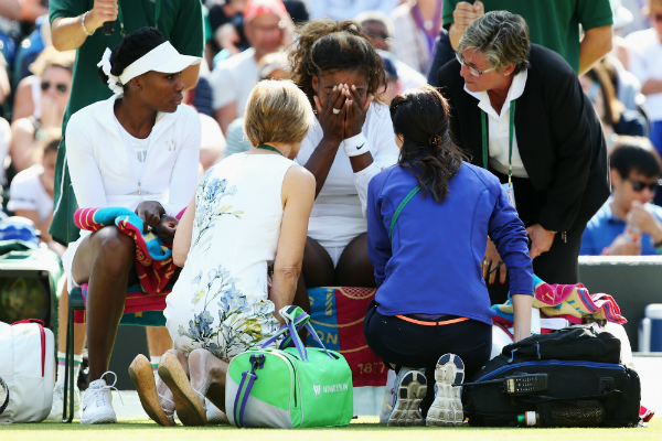 Serena Williams of the United States recieves treatment during the warm up before their Ladies Doubles second round match with Venus Williams (l) against Kristina Barrois of Germany and Stefanie Voegele of Switzerland on day eight of the Wimbledon Lawn Tennis Championships at the All England Lawn Tennis and Croquet Club on July 1, 2014 in London, England. (Photo by Jan Kruger/Getty Images)
