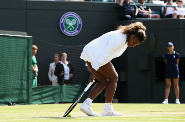 Serena Williams of the United States struggles during the warm up prior her Ladies Doubles second round match with Venus against Kristina Barrois of Germany and Stefanie Voegele of Switzerland on day eight of the Wimbledon Lawn Tennis Championships at the All England Lawn Tennis and Croquet Club on July 1, 2014 in London, England. (Photo by Jan Kruger/Getty Images)