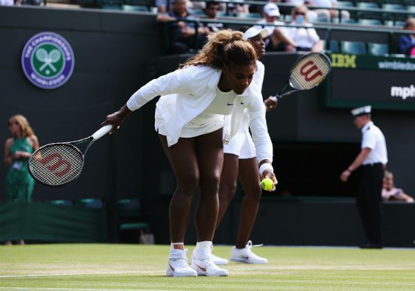 Serena Williams of the United States struggles during the warm up before her Ladies Doubles second round match with Venus Williams against Kristina Barrois of Germany and Stefanie Voegele of Switzerland on day eight of the Wimbledon Lawn Tennis Championships at the All England Lawn Tennis and Croquet Club on July 1, 2014 in London, England. (Photo by Jan Kruger/Getty Images)