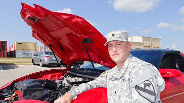 Spc. James Turner kneels by his pride and joy, a souped-up GM Pontiac Trans Am. Turner hopes to keep his family in the Killeen, Texas, community and work at a high-performance, racing garage.  Photo by Pat McKenna/Raytheon