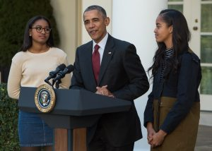 """US President Barack Obama speaks next to daughters Malia (R) and Sasha before """"pardoning"""" the National Thanksgiving Turkey.  (Photo credit NICHOLAS KAMM/AFP/Getty Images)"""
